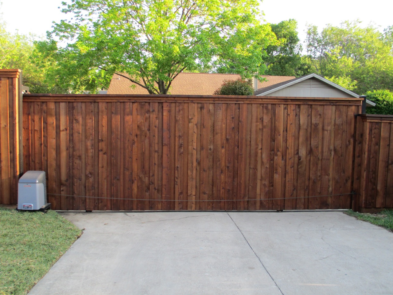 wood gates - wood board on board sliding gate at the entrance of concrete driveway