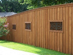 choosing a wood fence - stained wood fence with iron window details