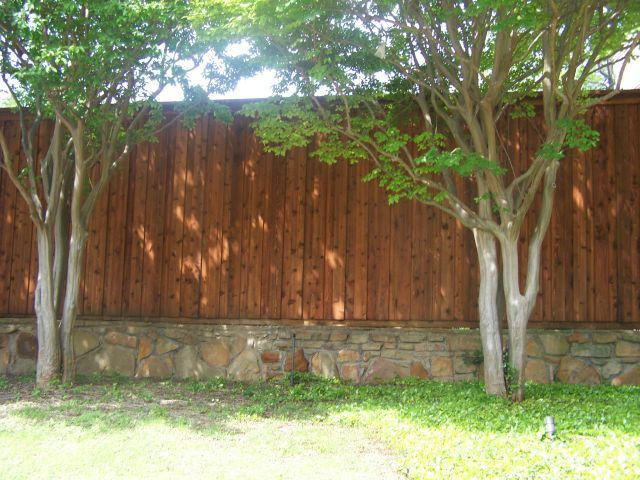 Cap Rail Board on Board Cedar Fence Stone Retaining Wall