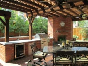 outdoor kitchen - outdoor kitchen space with wine cooler and fireplace