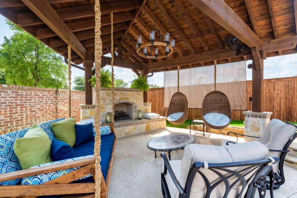 patio cover features - outdoor living space with bench swing and stone fireplace under wood patio cover