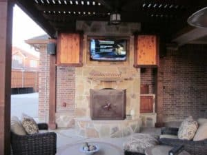 outdoor fire feature - fire place with television and outdoor seating