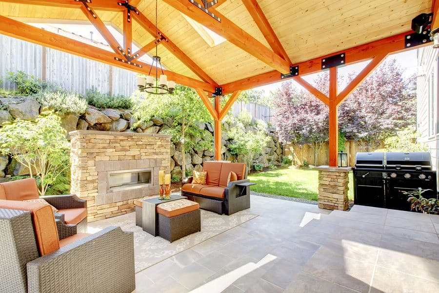 outdoor living space - outdoor living space with stone fireplace, seating and wood patio cover