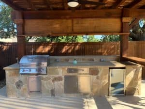 outdoor kitchen - stone outdoor kitchen with wood patio cover