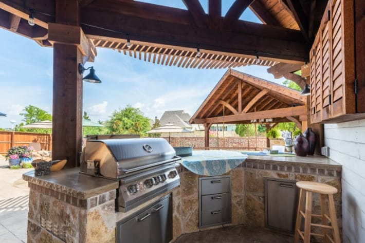 Outdoor Kitchen - stone outdoor kitchen with stainless steel appliances and wood patio cover