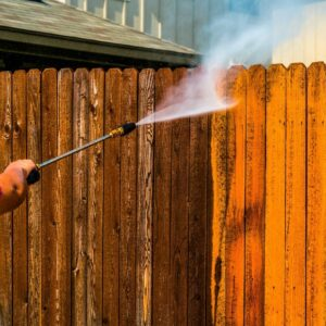 wood fence maintenance - man cleaning wood fence with power washer